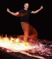Kursleiter Gregory Custodia geht über glühend heisse Kohlen. (Bild: PD)