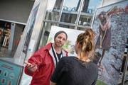 Roman Hagen von der Agentur Corris versucht, im Bahnhof Luzern eine Passantin zum Spenden zu animieren. (Bild: Pius Amrein (16. April 2018))