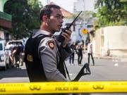 Ein indonesischer Polizist sichert den Tatort ab. Bei dem Selbstmordanschlag in der Grossstadt Surabaya wurden erneut Kinder eingesetzt. (Bild: Keystone/EPA/FULLY HANDOKO)