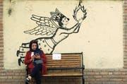 Eine Iranerin checkt ihr Smartphone; das Bild entstand Ende März in Teheran. (Bild: Abedin Taherkenareh/EPA)