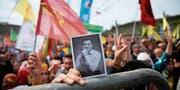 Eine Oppositionelle hält in Istanbul ein Foto des inhaftierten Selahattin Demirtas hoch. Der Kurdenpolitiker wartet seit fast eineinhalb Jahren auf einen Prozess. (Bild: Lefteris Pitarakis/AP (21. März 2018))