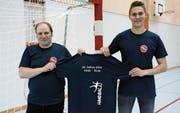 Marcel Krüsi, Präsident des BSV Bischofszell, und Pascal Häderli, Verantwortlicher für die Öffentlichkeitsarbeit des BSV, präsentieren in der Sporthalle Bruggwiesen das Jubiläums-T-Shirt. (Bild: Georg Stelzner)