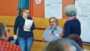 Zwei Zukunftskonferenz-Teilnehmerinnen und Genossenschaftsgeschäftsführer Martin Schmidli (mit Mikrofon) präsentieren im Plenum Resultate aus einer Gruppenarbeit. (Bild: Mathias Frei)