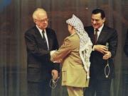 Seltener Moment der Hoffnung im Nahen Osten: Israels Ministerpräsident Yitzhak Rabin und PLO-Chef Yassir Arafat geben sich 1994 in Ägypten neben Präsident Hosni Mubarak die Hand. (Bild: Michel Euler/AP (Kairo, 4. Mai 1994)