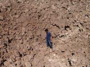 Ein Mann in einem durch eine abgeworfene Bombe entstandenen Krater in Sarakeb. In der syrischen Stadt soll bei einem Angriff am 4. Februar Giftgas eingesetzt worden sein. (Bild: Keystone/AP The Committee of Jabal al-Zawiyah, Jisr el-Sheghour,)
