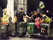 Polizisten verladen dutzende Kisten und Koffer voller Luxusartikel, die bei einer Razzia bei Malaysias Ex-Regierungschef Najib gefunden wurden. (Bild: KEYSTONE/AP)