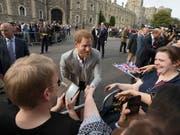 Prinz Harry begrüsst am Vorabend seiner Hochzeit bereits für das Fest versammelte Fans vor Schloss Windsor. (Bild: KEYSTONE/AP/PETER DEJONG)