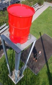 Signerbrunnen in St.Gallen. Der starke, satte Wasserstrahl aus dem roten Fass klatscht auf den schwarzen Asphalt, und zerstiebt in tausend Tropfen.