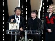 "Regisseur Hirokazu Kore-Eda nimmt in Cannes die Goldene Palme für sein berührendes Familiendrama ""Shoplifters"" entgegen. (Bild: KEYSTONE/EPA/SEBASTIEN NOGIER)"
