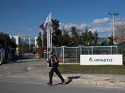 Ein Mann überquert vor der Novartis-Niederlassung in Athen eine Strasse. Dem Basler Pharmakonzern wird vorgeworfen, in Griechenland Ärzte und Politiker bestochen zu haben. (Bild: Keystone/AP/PETROS GIANNAKOURIS)