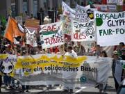 """Mehr als 2000 Personen haben am Samstag in Basel gegen die """"zerstörerische Macht der Agrokonzerne"""" protestiert. Sie fordern einen Richtungswechsel in der Landwirtschaftspolitik. (Bild: Keystone/GEORGIOS KEFALAS)"""