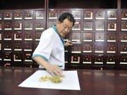 Ein chinesischer Pharmazeut bereitet Traditionelle Chinesische Medizin vor. Die Arzneimittel aus anderen Kulturkreisen können hochaktive Substanzen mit gefährlichen Nebenwirkungen enthalten, wie Forschende der Universität Basel herausgefunden haben. (Bild: KEYSTONE/EPA/WU HONG)
