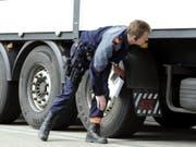 Ein Polizist kontrolliert einen Lastwagen anlässlich einer Car- und Schwerverkehrskontrolle der Kantonspolizei Zürich. (Bild: Keystone/WALTER BIERI)