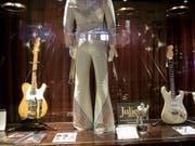 Auch sie wurden versteigert: Ein Bühnenkostüm von Pop-Sänger Elton John (m) und eine Gitarre (l), die Bob Dylan in einer entscheidenden Phase seiner Musik-Karriere begleitete. (Bild: Keystone/AP/MARK LENNIHAN)