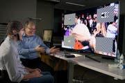 Martin Biallas (rechts) erklärt Testperson Beat Bösch wie er mit seinen Hirnströmen einen TV steuern kann. (Bild: Corinne Glanzmann; Nottwil, 17. Mai 2018)