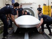 """Das Entwicklungsteam von Swissloop mit dem neuen Prototypen """"Mujinga"""" von Swissloop. In Zukunft sollen Transportkapseln Güter schneller und umweltschonender von A nach B befördern. (Bild: KEYSTONE/PATRICK HUERLIMANN)"""
