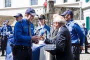 Polizist Dominik Ettlin erhält nach der Vereidigung in Sursee von Polizeiseelsorger Robert Knüsel ein Teelicht. (Bild: Manuela Jans-Koch, 24. Mai 2018)