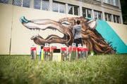 Künstler Linus von Moos bei seiner Arbeit vor der ZHB. (Bild:Queenkong/ Vero Schmid)
