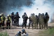 Einsatzkräfte der Polizeikorps von Luzern, Nid- und Obwalden schützen sich bei der Übung vor Tränengas (oben). Danach bringen sie Feuerwehrleute in Sicherheit. (Bild: Corinne Glanzmann; Schüpfheim, 25. Mai 2018)