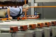 Ein Mitarbeiter überprüft eine Maschine in einer Textildruckerei. Bild: Christian Beutler/Keystone (15. Juli 2014)