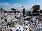 Verwüstung ohne Ende: Ein Mann filmt in der Nähe von Damaskus die Ruinen eines Forschungszentrums, das zuvor durch ausländische Streitkräfte zerbombt wurde. (Bild: Keystone/AP/HASSAN AMMAR)