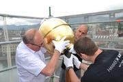 Oskar Näpflin (links) mit weiteren Mitarbeitern der Firma Muff Kirchturmtechnik AG Triengen beim Befestigen der Goldkugel auf der Kirchturmspitze. Bild :Hugo Bischof (Luzern, 29. Mai 2018)