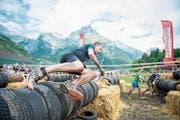 Ein Strongmanrun-Teilnehmer springt über die Reifenmauer. Bild: Roger Grütter (Engelberg, 3. Juni 2017)