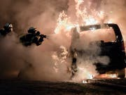 Feuerwehrleute löschen bei den Krawallen rund um den G20-Gipfel von 2017 in Hamburg ein brennendes Auto. Elf Monate später sind in mehreren Ländern Verdächtige befragt worden, auch in der Schweiz. (Bild: KEYSTONE/EPA/CLEMENS BILAN)