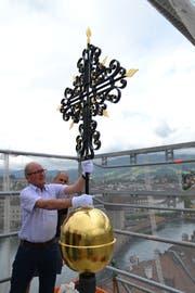 Oskar Näpflin befestigt die Goldkugel mit Kreuz definitiv auf der Spitze des Kirchturms der Peterskapelle. Bild: Hugo Bischof (Luzern, 29. Mai 2018)