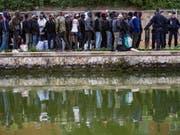 Flüchtlinge stehen Schlange, um in Unterkünfte in Paris oder der Umgebung gebracht zu werden. Seit Monaten hatten sich immer mehr Migranten an den Ufern zweier Kanäle im Nordosten der französischen Hauptstadt angesiedelt. (Bild: Keystone/EPA/IAN LANGSDON)