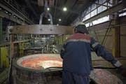 Ein Mitarbeiter der Trimet Aluminium SE entfernt Schmutz aus geschmolzenem Aluminium. (Bild: Jasper Juinen/Bloomberg (Essen, 4. Mai 2018))