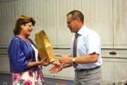 Gemeindepräsidentin Heidi Grau überreicht Thomas Friederich am Ende der Gemeindeversammlung ein Geschenk. (Bild: Georg Stelzner)