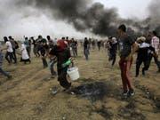 Palästinensische Demonstranten im Gazastreifen versuchen sich vor Tränengas der israelischen Armee zu retten. (Bild: KEYSTONE/AP/ADEL HANA)