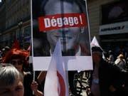 """""""Hau ab!"""" steht auf einem Protestplakat mit dem Konterfei von Präsident Emmanuel Macron, das Demonstranten am Samstag in Paris tragen. (Bild: KEYSTONE/AP/FRANCOIS MORI)"""
