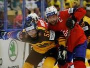 Norwegens Jonas Holös von Fribourg-Gottéron (rechts) kämpft gegen Deutschlands Markus Eisenschmid um den Puck (Bild: KEYSTONE/AP/PETR DAVID JOSEK)