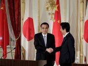 Handschlag als Symbol für das Tauwetter zwischen Peking und Tokio: Der japanische Premierminister Shinzo Abe (r) und sein chinesischer Amtskollege Li Keqiang (l) an einer gemeinsamen Medienkonferenz in Tokio. (Bild: Keystone/AP POOL Bloomberg/KIYOSHI OTA)