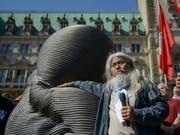 """Der taiwanesische Künstler Kang Mu-Xiang letzte Woche mit einer 1,5 Tonnen schweren """"Embryo""""-Skulptur aus recycleten Liftkabeln - genannt """"Unlimited Life"""" - in Hamburg. Weitere solche Skulpturen stehen derzeit auch am New Yorker Broadway. (Bild: Keystone/DPA/AXEL HEIMKEN)"""
