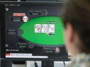 Ein Mann spielt auf der Webseite des ausländischen Glücksspielanbieters Pokerstars Online-Poker. Künftig werden Angebote von ausländischen Anbietern verboten und für Spieler in der Schweiz im Internet gesperrt. Einzig Schweizer Casinos wird das Anbieten von Online-Geldspielen erlaubt sein. (Bild: Keystone/GAETAN BALLY)