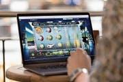 Ein Mann spielt auf einer Online-Casino-Seite auf seinem Computer am Zürcher Hauptbahnhof. (Bild: Gaëtan Bally/Keystone, 12. April 2018)