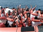 Flüchtlinge von der «Aquarius» winken, nachdem sie auf ein Boot der italienischen Küstenwache gebracht wurden. (Bild: Keystone/AP SOS Mediterranee/KENNY KARPOV)