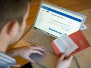 Ein Mann studiert am Laptop die Unterlagen für eine Abstimmung per e-Voting (Bild: KEYSTONE/ALESSANDRO DELLA BELLA)