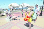 Touristen lassen sich vor dem Olympiastadion Sotschi mit dem offiziellen WM-Maskottchen «Zabivaka» ablichten. Bild: EPA
