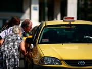 Ein älteres Paar sucht in Athen nach einem leeren Taxi. In der griechischen Hauptstadt und in Thessaloniki sind die Taxifahrer am Mittwoch in einen 24-stündigen Streik getreten. (Bild: Keystone/EPA/ALKIS KONSTANTINIDIS)