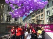 Frauen fordern Lohngleichheit und lassen lila Ballone in den St. Galler Himmel steigen. (Bild: Keystone-SDA: Nathalie Grand)