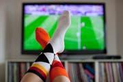 Hoch die Füsse: Wenn Fussball-WM ist, ist die eine Hälfte der Bevölkerung hin und weg - die andere Hälfte schaut gelangweilt weg. (Keystone)