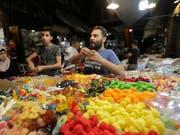 Die Menschen in Syrien decken sich auf einem Markt in Damaskus mit Süssigkeiten ein für Eid al-Fitr, das Fastenbrechen nach dem Ramadan. (Bild: KEYSTONE/EPA/YOUSSEF BADAWI)