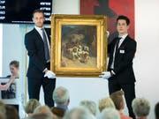 Mitarbeitende der Galerie Kornfeld präsentierten am Freitag dem Auktionspublikum das Gemälde «Die Gotthardpost» von Rudolf Koller. Einen Abnehmer fand das Bild aber nicht. (Bild: KEYSTONE/PETER KLAUNZER)