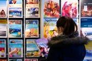 Eine Kundin studiert die Kataloge des Reisebüros Meile AG. Bild: Michel Canonica