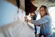 Führt eine alte Familientradition weiter: Trix Limacher bringt Holzschindeln an einer Fassade an. (Bild: Corinne Glanzmann (Alpnach, 14. Juni 2018))
