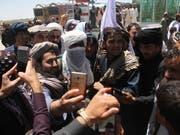 Unbewaffnete Taliban-Kämpfer umringt von Sympathisanten in Ghazni (Bild: KEYSTONE/EPA/STR)
